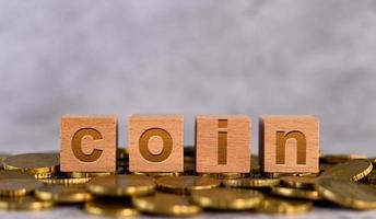 Alfabeto letras cúbicas de madeira em moedas de ouro foto