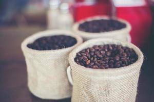 saco de grãos de café em fundo de madeira foto