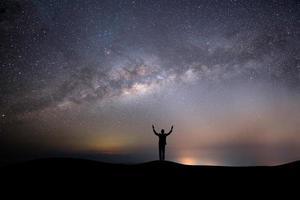 silhueta de uma pessoa no topo de uma colina com estrelas