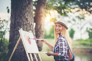 linda garota fazendo um desenho no parque
