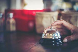 mão tocando campainha de prata em cafeteria