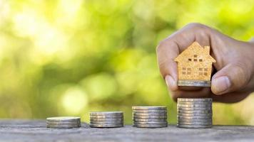 modelo de casa de madeira em moedas e mãos de pessoas, ideias de investimento imobiliário e transações financeiras foto