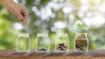 plantar árvores em garrafas transparentes para economizar dinheiro em uma mesa de madeira e ideias de crescimento de negócios de fundo verde borrado foto