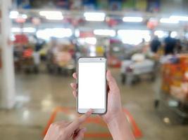 mão usando um telefone móvel inteligente de tela em branco com fundo desfocado no supermercado foto