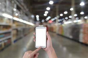 mãos usando um telefone móvel inteligente de tela em branco com fundo desfocado no supermercado foto
