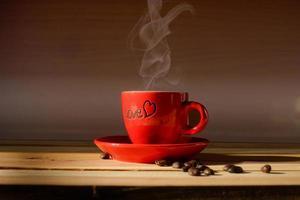 xícara de café vermelha em madeira com grãos de café foto