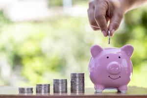close-up de uma mulher colocando uma moeda em um cofrinho, incluindo uma pilha de moedas, salvando ideias e crescimento financeiro foto