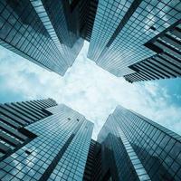 edifícios de escritórios reflexivos de vidro contra o céu azul com nuvens e luz do sol