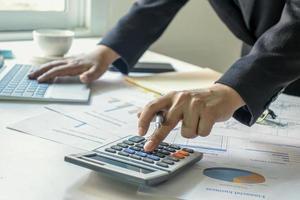 empresários usam uma calculadora para verificar suas informações financeiras, ideias de trabalho e estratégias de trabalho em equipe foto