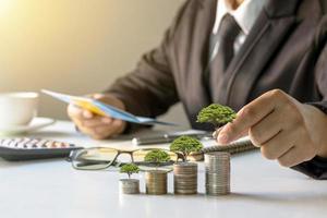 empresários plantando árvores em uma pilha de ideias para economizar dinheiro e investindo no futuro