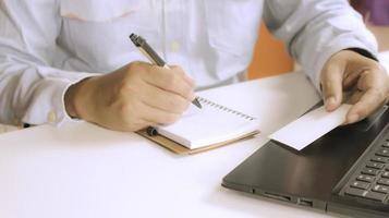 pessoa fazendo anotações em uma mesa