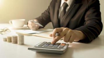 gerenciamento de contas e conceito de economia de dinheiro, um close-up de uma mulher usando uma calculadora para produzir relatórios de trabalho de contabilidade foto