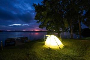 tenda amarela brilhante perto da água ao pôr do sol