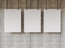três pôsteres em branco pendurados na velha parede de cimento
