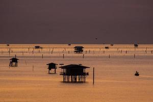 silhuetas de cabanas flutuantes em sunirse foto