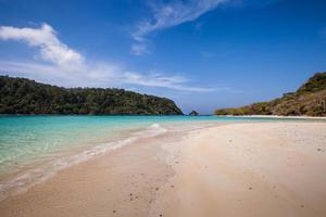 praia de areia branca e água azul foto