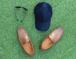 chapéu, sapatos e óculos de sol na grama