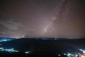 Via Láctea e luzes da cidade foto