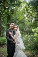 noiva e noivo em pé com fundo verde do parque natural foto