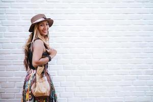 mulher caminhando perto de uma parede de tijolos