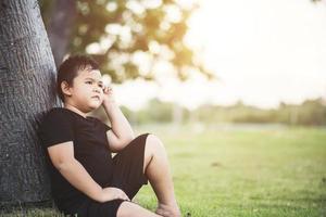 garotinho sentado debaixo da árvore pensando foto