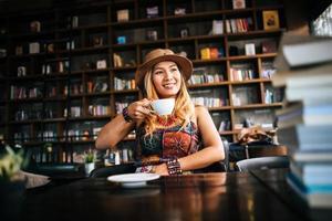 mulher bebendo cappuccino e lendo um livro