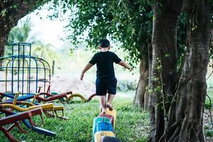 criança correndo com pneus no playground foto