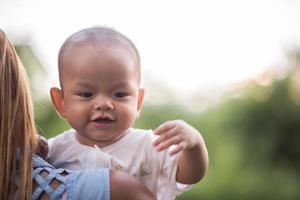 mãe e bebê rindo e brincando no parque foto
