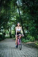 retrato de uma mulher com uma bicicleta rosa no parque foto