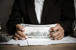 mãos contando notas de dólar
