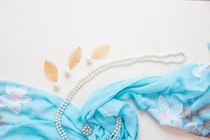 vista superior do tecido azul, pérolas e batom foto