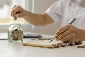 a mão de um empresário que faz anotações em um caderno, inclusive para economizar dinheiro, a ideia de fazer informações financeiras em casa