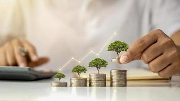 um empresário segurando uma moeda com uma árvore que cresce e uma árvore que cresce em uma pilha de dinheiro. a ideia de maximizar o lucro do investimento empresarial foto