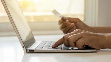 mão de mulheres jovens usando um laptop para fazer compras online e transferir dinheiro de cartão de crédito online conceito de banco