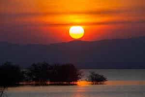 pôr do sol colorido sobre árvores e água
