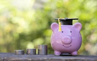 chapéus de pós-graduação colocados em cofrinhos e moedas empilhadas no chão de madeira. ideias de educação e economia educacional