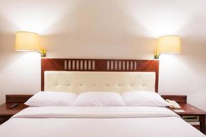 cama de hotel com lâmpadas de cabeceira foto