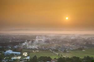 nascer do sol nebuloso sobre uma cidade foto