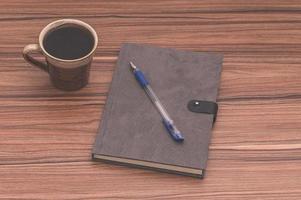 caneca de café e caderno na mesa foto