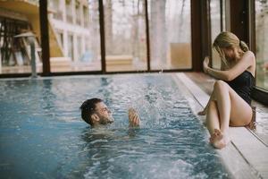 jovem casal relaxando à beira da piscina interior foto