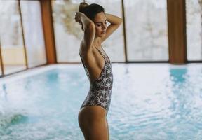 bela jovem em pé à beira da piscina