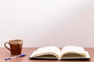 caneca de café e caderno vazio na mesa foto