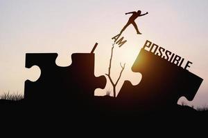 homem pulando peças do quebra-cabeça do impossível para o possível foto