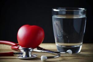 estetoscópio e água potável com coração vermelho foto