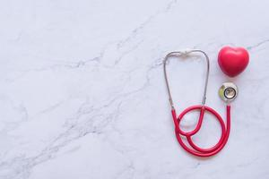 coração vermelho e estetoscópio sobre fundo de mármore branco foto