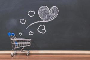 um pequeno carrinho de compras e rabiscos de coração em um quadro negro