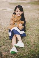 linda garota asiática com ursinho de pelúcia sentado em um campo foto