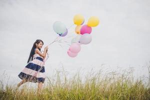 menina brincando com balões no campo de prados