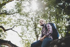 homem jovem hippie sentado em um galho de árvore no parque foto