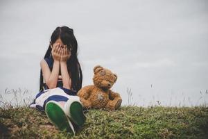 menina sentada com seu urso chateada